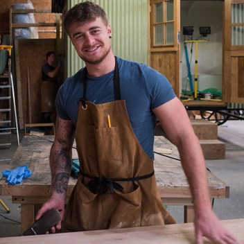 Master hutmaker Rikki in the Plankbridge workshop happily smiling at the camera