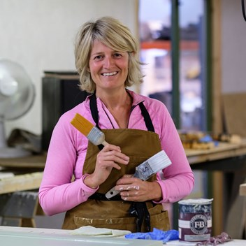 Gail in the Plankbridge paint shop holding brushes smiling at the camera