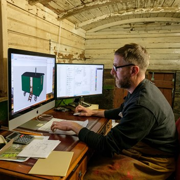 Plankbridge draughtsman Mark doing CAD drawings in the vintage living van drawing office
