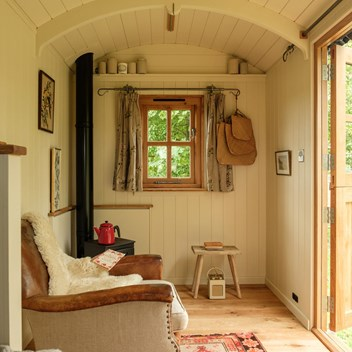 Snug shepherd's hut interior, a favourite image with a leather chair, curtains and view of trees beyond