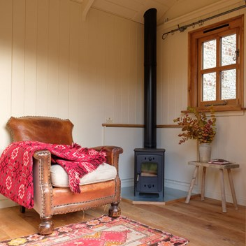 Shepherd's hut interior with wood burner and leather chair with red blanket throw