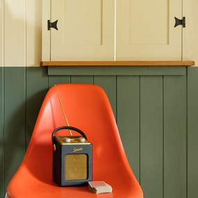 Orange chair in shepherd's hut with vintage radio and closed painted shutters above