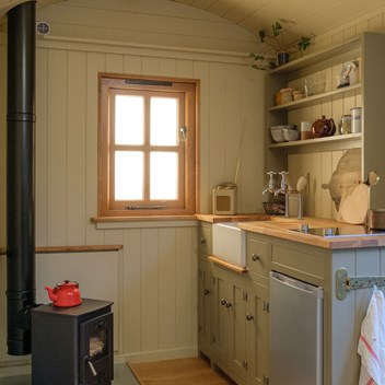 Shepherd's hut cabin interior with a painted kitchen dresser and wood burner with plates and chopping boards displayed