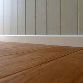 Solid oak floor in a Plankbridge shepherds hut with skirting board and painted wall behind