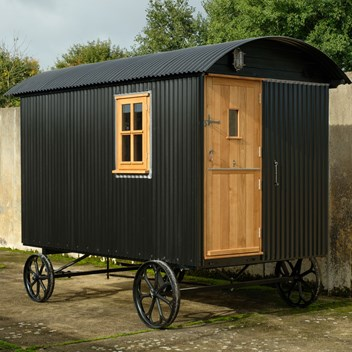 A traditional shepherd's hut in black cladding with oak door and window