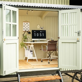 Cabin shepherd's hut office looking in to the desk with computer and office chair