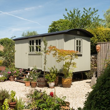 A Plankbridge Cabin in a Lichen colour, with double doors on a gravel base and lovely planting