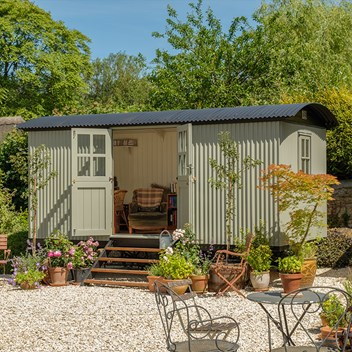 Plankbridge Cabin shepherd's hut in garden with garden chairs and table, on a gravel base