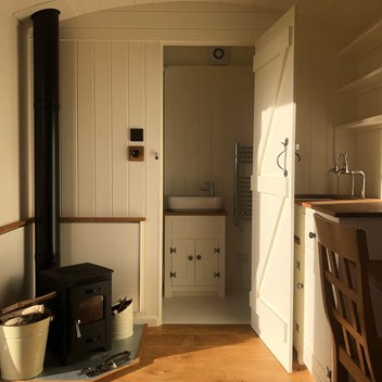 View towards the bathroom end of a shepherd's hut with woodturner to left and washbasin next to a shower