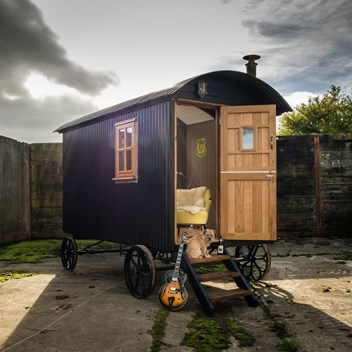 Exterior view of a black painted shepherd's hut with guitar and evening sun behind
