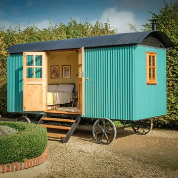 External view of a shepherd's hut in teal blue and double doors and bed inside