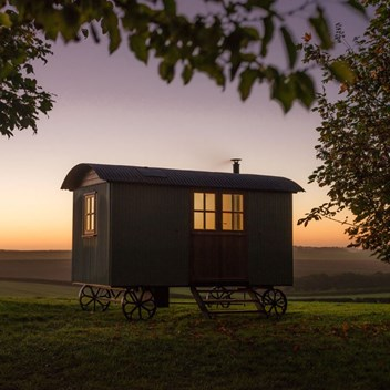 A shepherd's hut at dawn, with the sun rising over the Dorset hills behind
