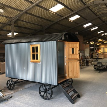 External view of The Snug shepherds hut in the workshop with oak door and window